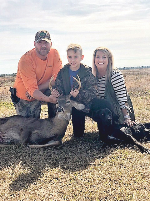 Kahler Brace, age 8, got his first buck. He is pictured with his parents, Chris and Shelly, and dog Lexi who helped track and find the deer.