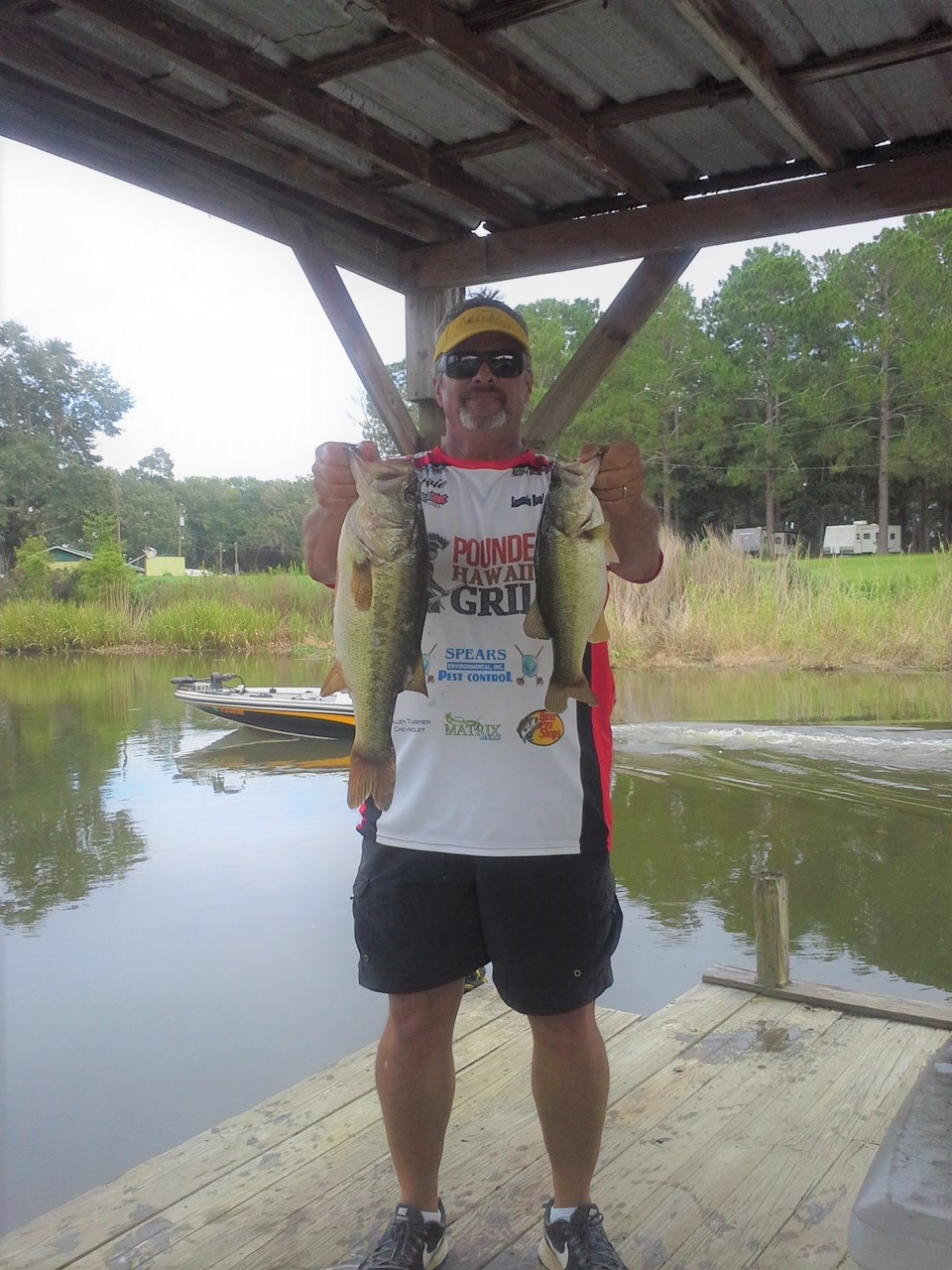 Ernie Martin holding two topwater bass caught on Lake Seminole.