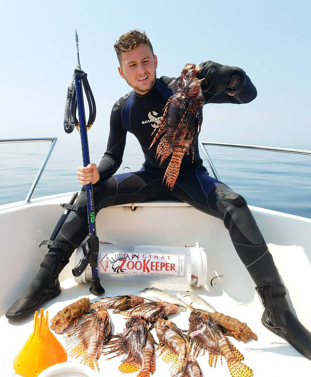 With a ZooKeeper lionfish containment unit by his side, lionfish hunter Tristan Lennard shows off his haul from a recent dive – including this personal best 17-inch fish.
