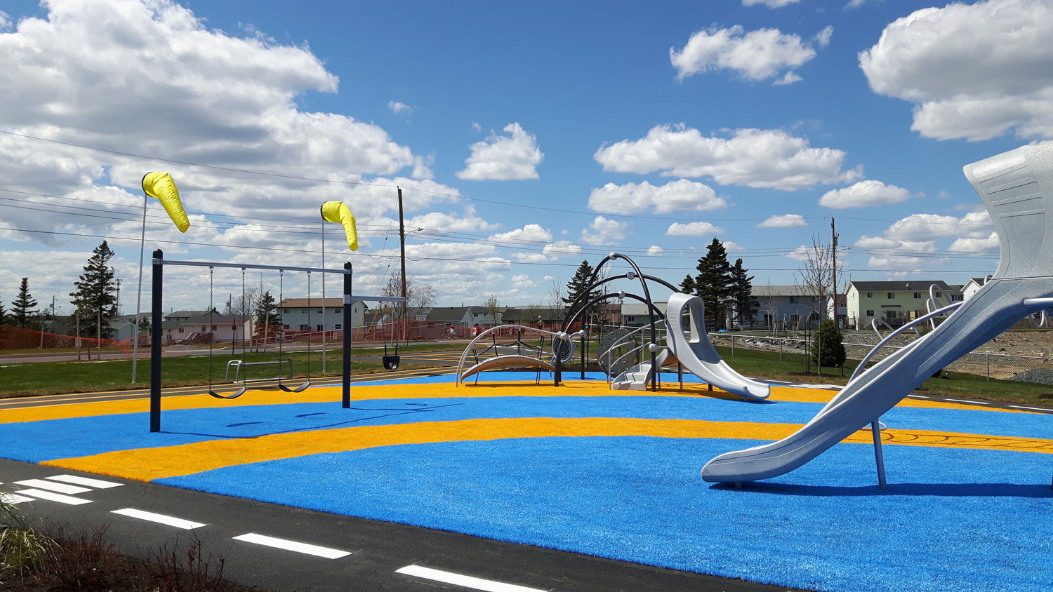 Colourful playground surfacing contrasts with industrial-coloured play equipment.