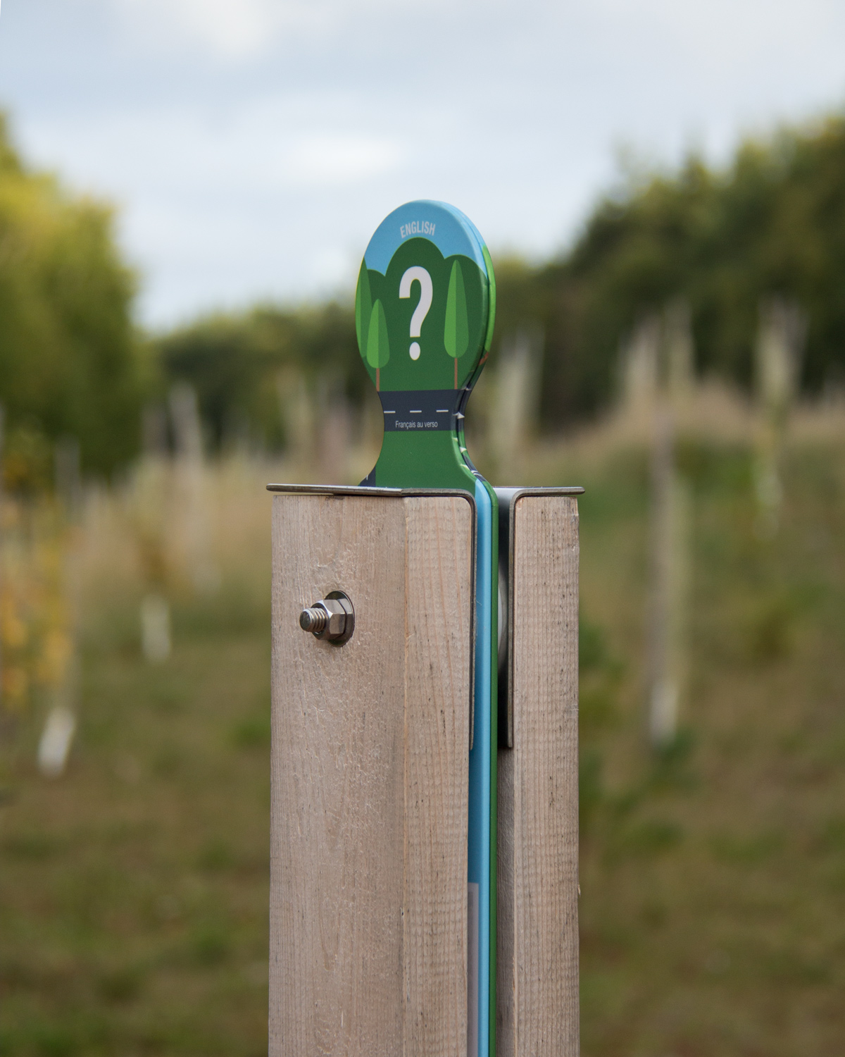 A SIMPLE MARKER Wooden posts adorned with a simple graphic element indicate locations of interpretive content.