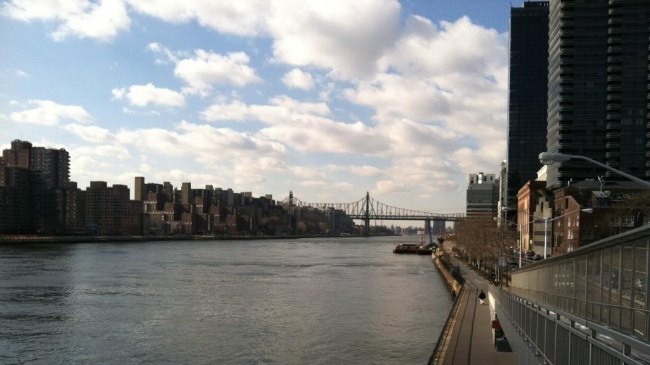 Looking south along the East River, below a blue sky with fluffy white clouds.