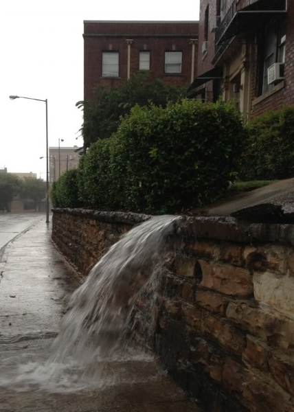 Water sluiced down onto the sidewalk in impromptu waterfalls as the rainfall became more and more heavy.