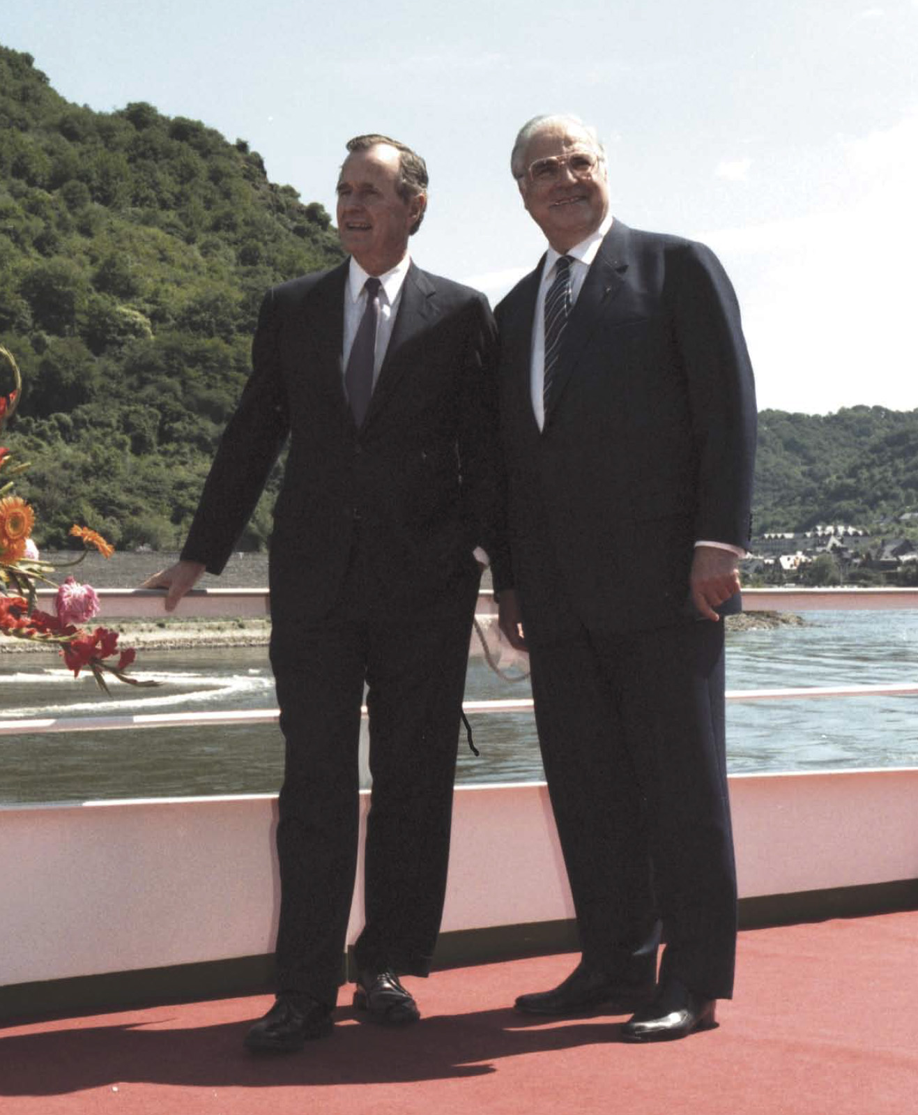 """President Bush and Chancellor Helmut Kohl aboard the riverboat Stolzenfels as they cruise the Rhine River, West Germany on May 31, 1989. President Bush's excellent personal relationship with Chancellor Kohl was the prerequisite for Kohl's daring moves for German reunification in late 1989 and 1990. Bush encouraged Kohl's political ambitions and thus became the """"godfather"""" of German reunification."""