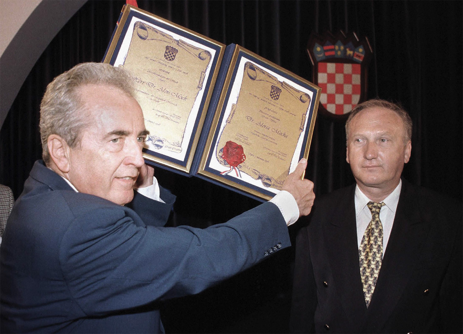 "For his crucial role in the Croatian independence struggle of 1991, former Austrian Minister of Foreign Affairs Alois Mock (left) holds the document after being announced ""Honoured Citizen of Split"", Croatia, Friday, Aug. 7,1998. Ivan Skaric, the mayor of Split (right) confers   the honor."