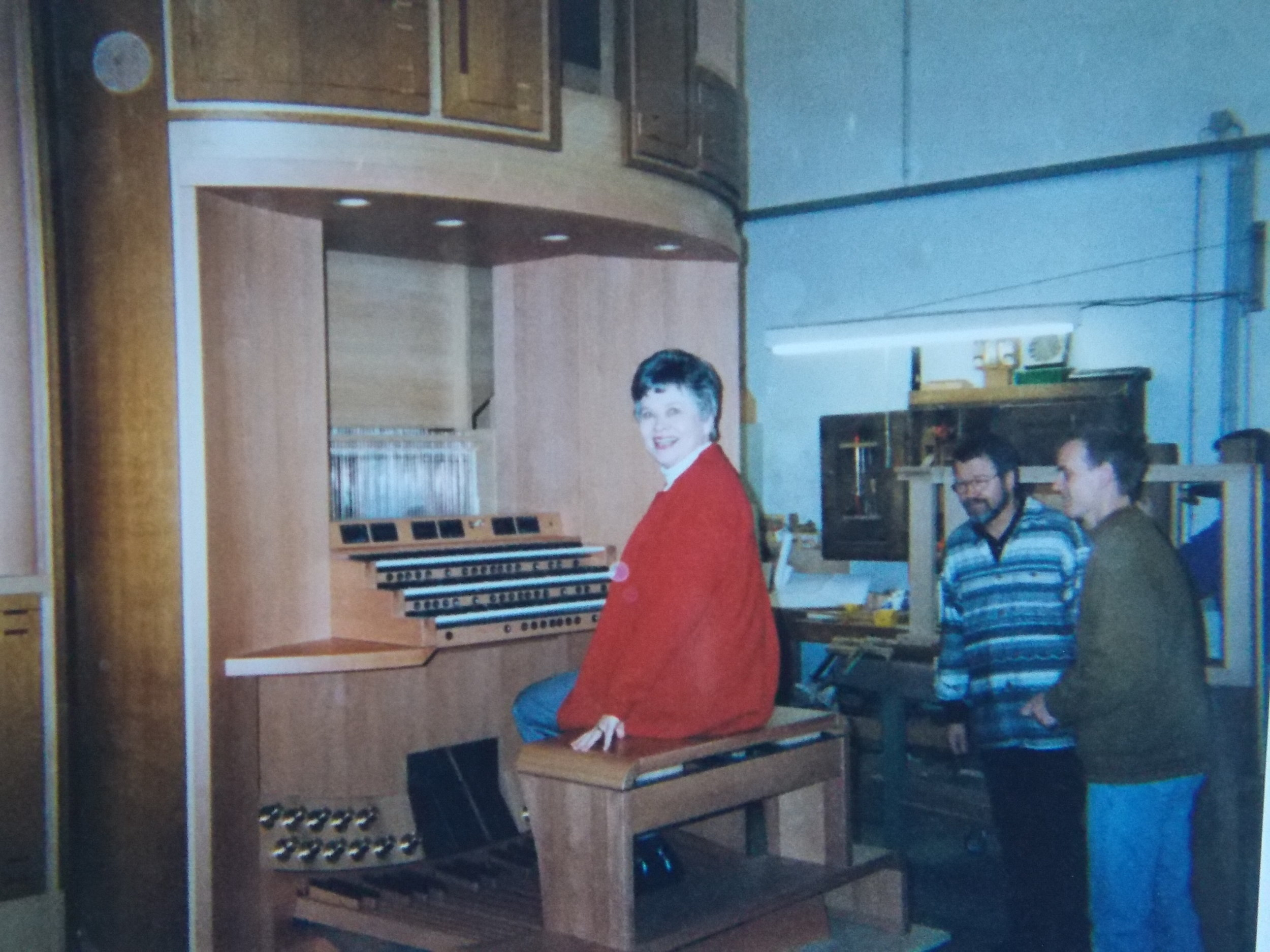 "Becky Ogle, seated, surveys the new organ in its ""birthplace"" in Owingen, Germany, shortly before it was disassembled and shipped to the U.S. Behind her are owner, Caspar von Glatter-Götz (left) and his partner, Heinz Kremnitzer, who headed up the installation of the organ once it arrived in Palos Verdes."
