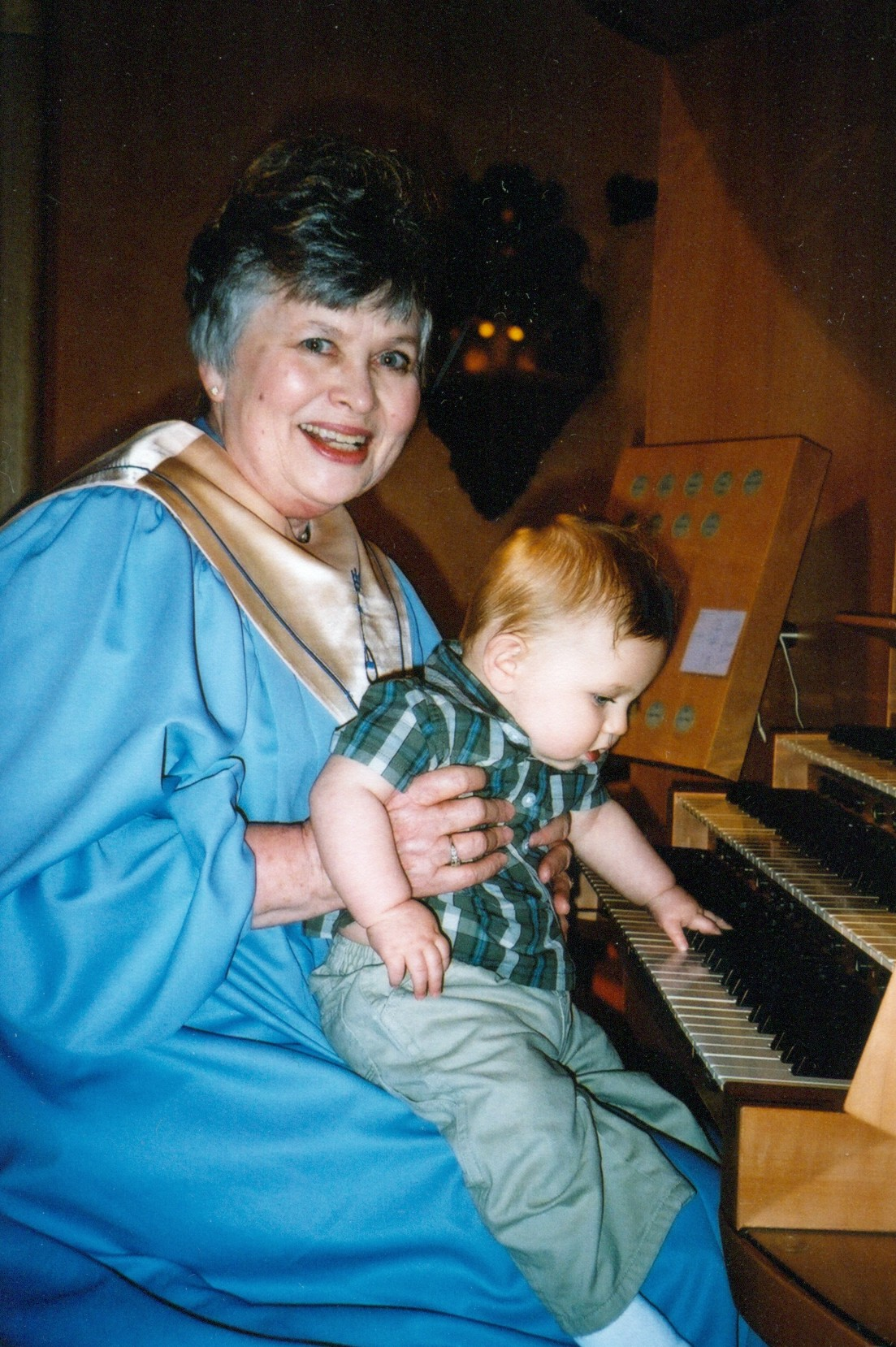 Becky with grandson at the organ in June, 2011