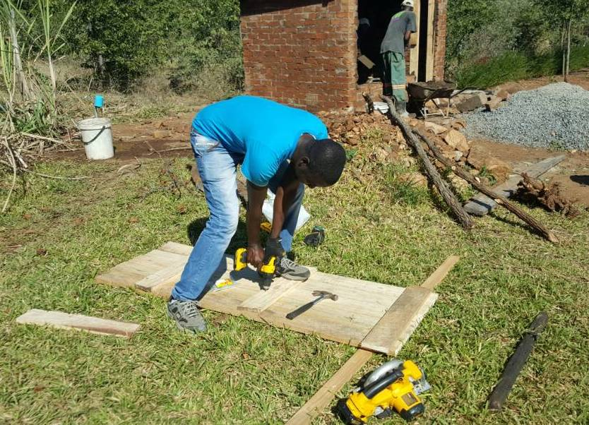 Shepherd Zhou builds a chicken coop on new land owned by Joyous Christian Church