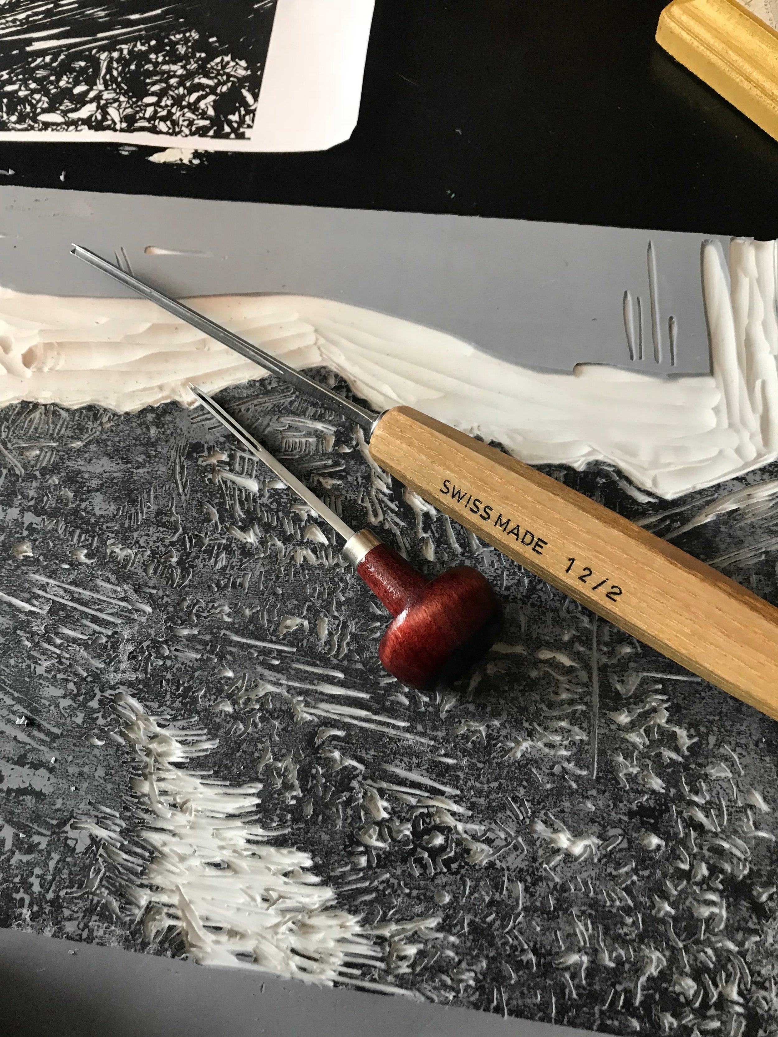 A closer look of the carving process. You can see I'm carving away everything I don't want to be inked. This linoleum will give a contrast when carving to help with that and to know when you made a deep enough gouge that it won't be inked.