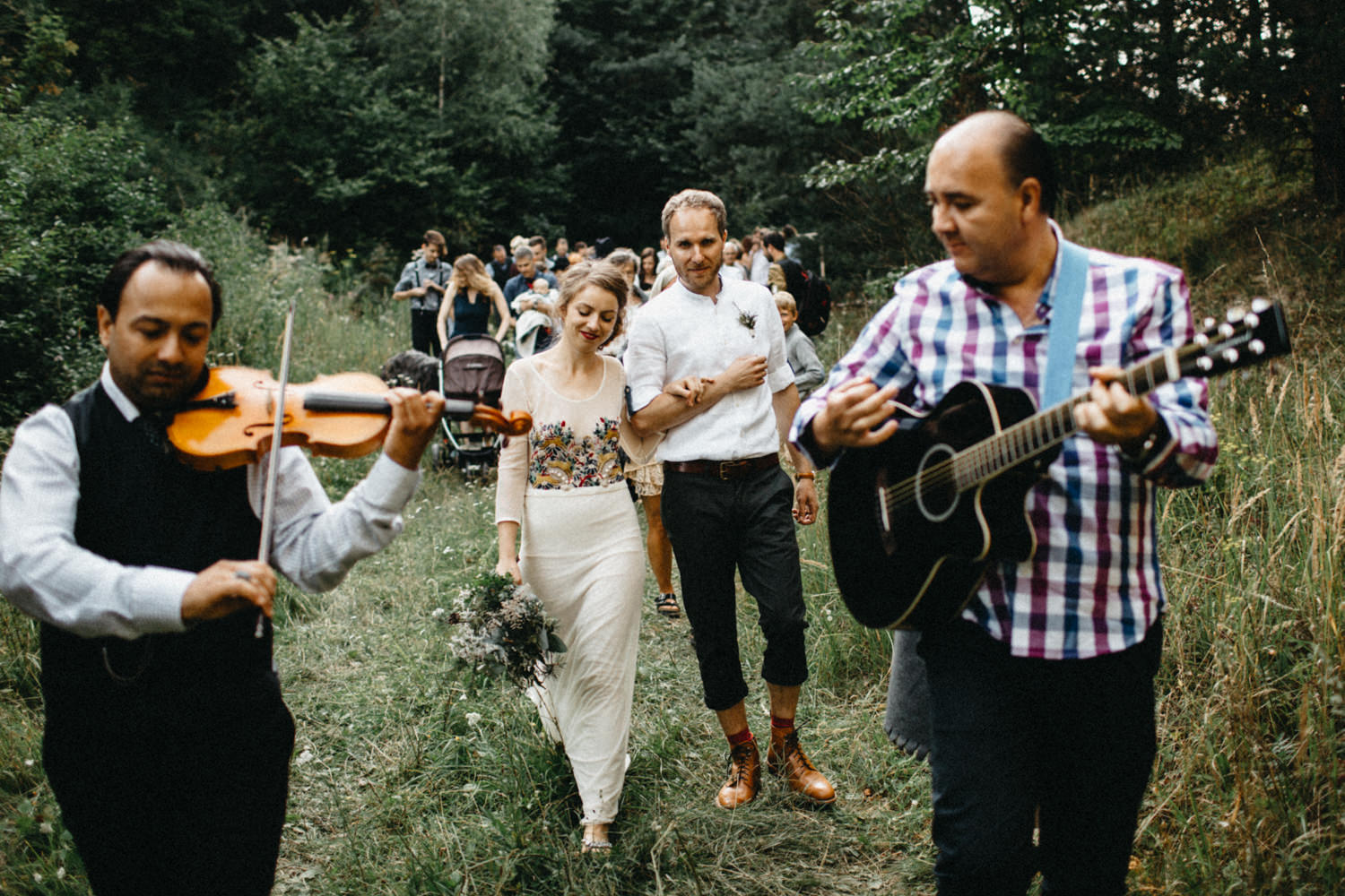 bride and groom exiting the ceremony location with live music