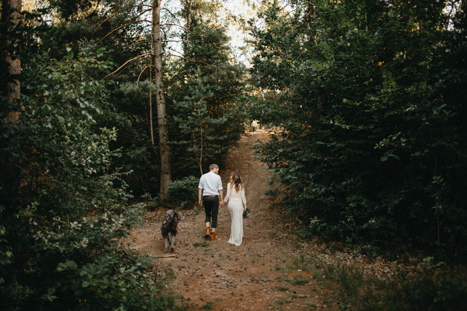 husband and wife walking through the forest