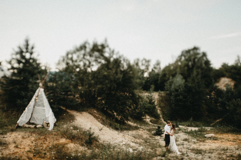 boho setup, bride and groom next to a tent