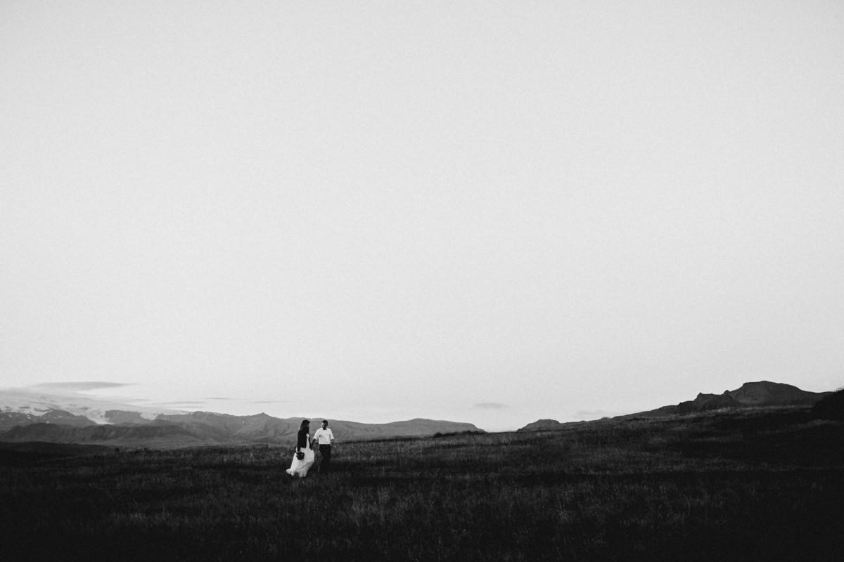 bride and groom running around lava fields