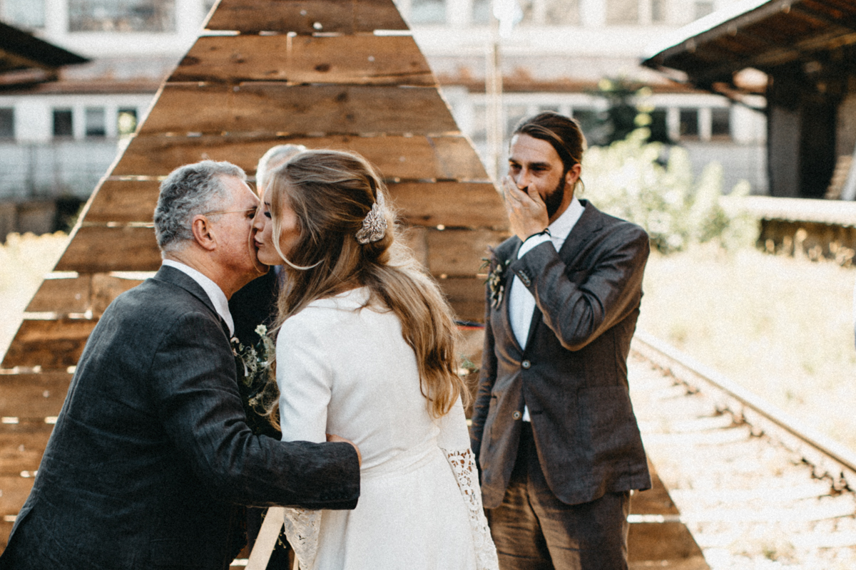dad giving the bride a kiss, groom watching