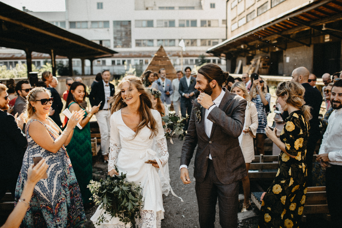 guests clapping while bride walks away