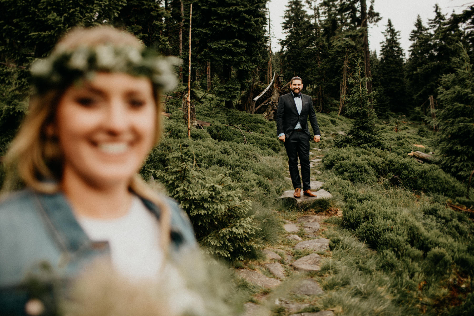 groom looking at his bride in the forest