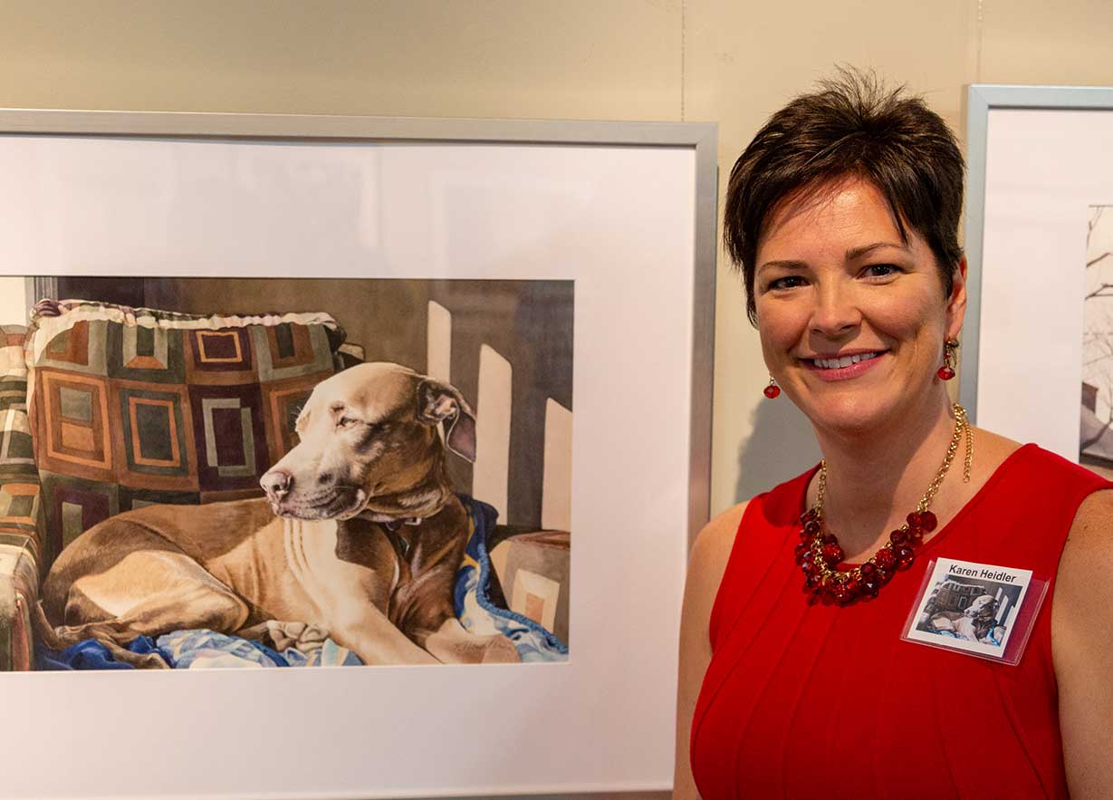 Karen Heidler, of Brooksville, Florida, poses with her painting at the exhibition