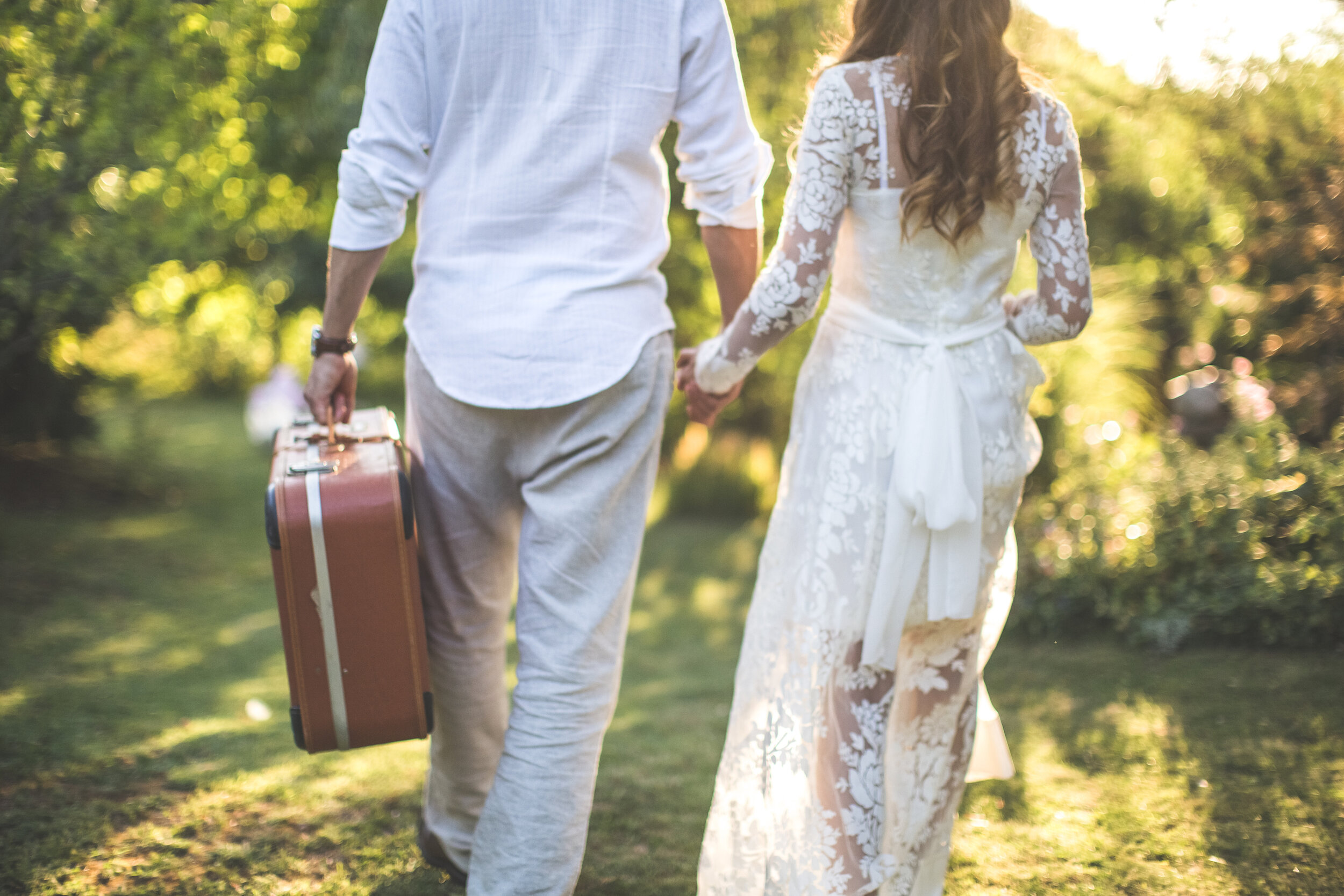 bride and groom holding hands carrying luggage.jpg