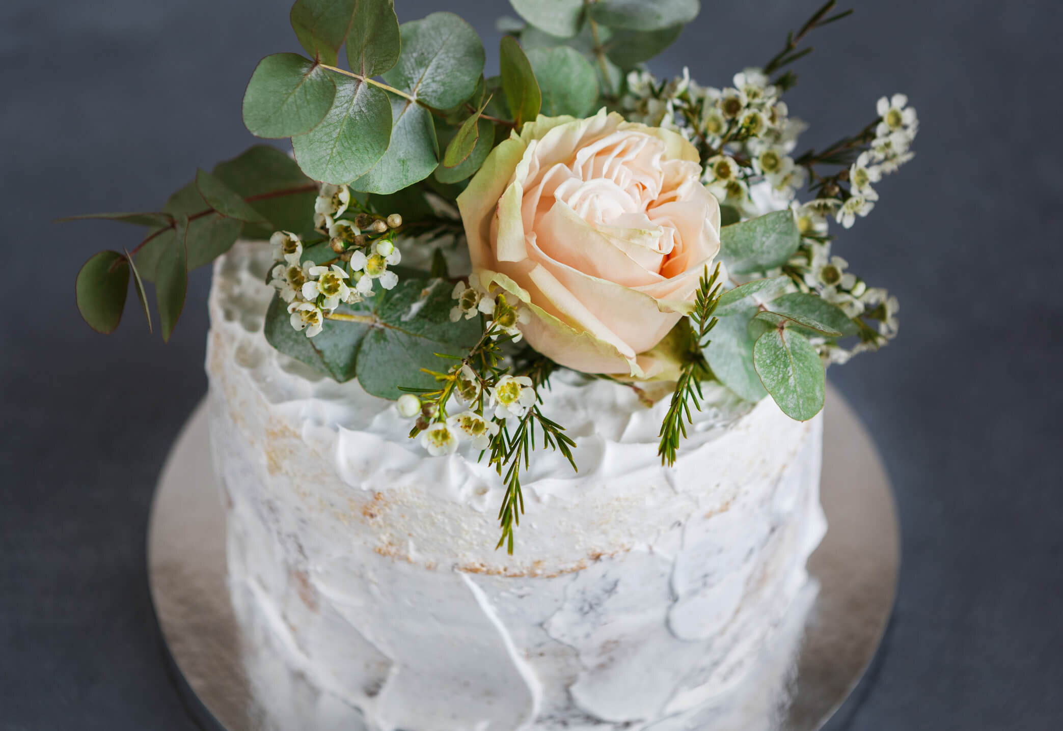 Wedding cake with white frosting and pink flower.jpg
