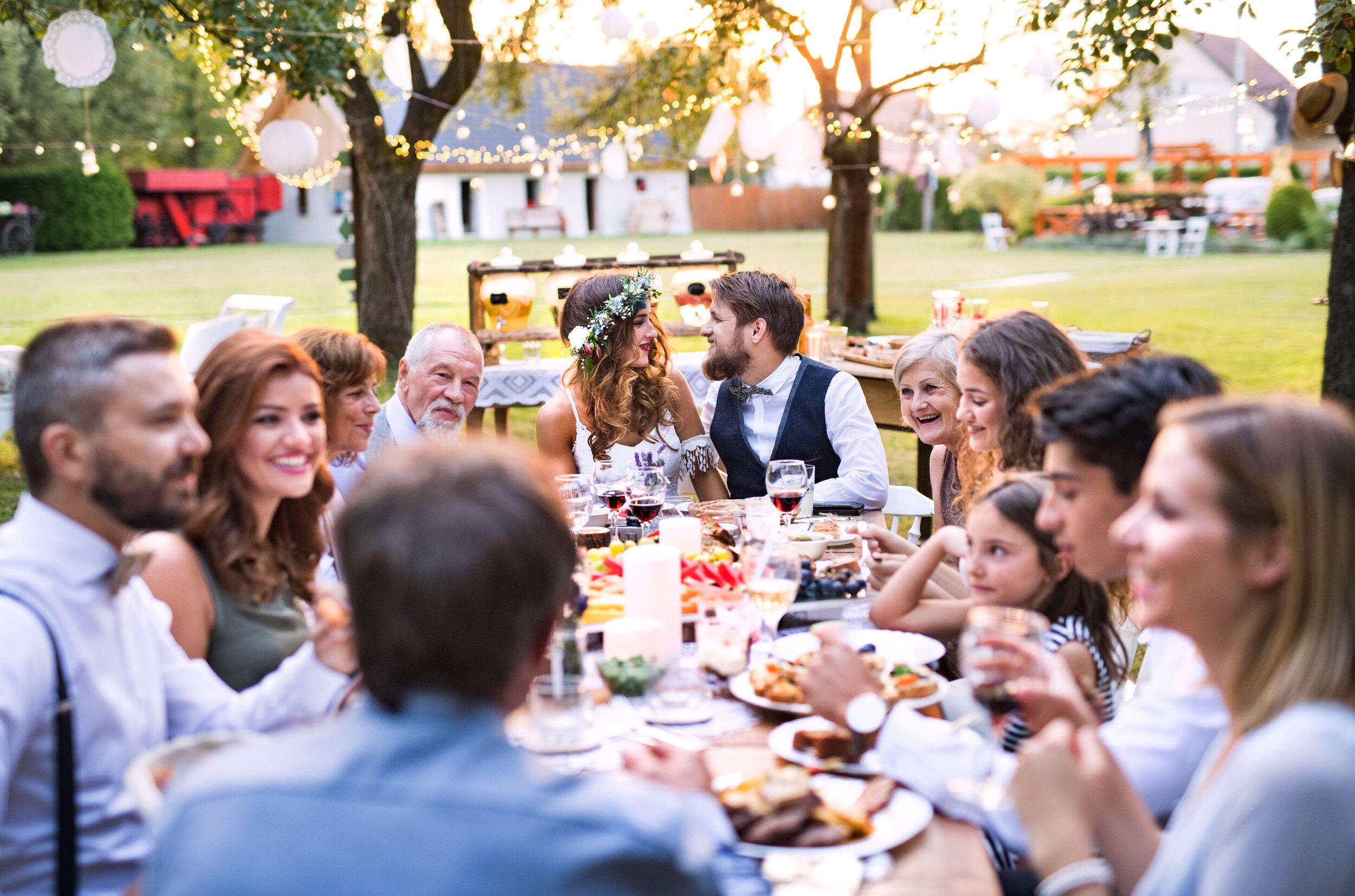 Table of people eating dinner at backyard wedding.jpg