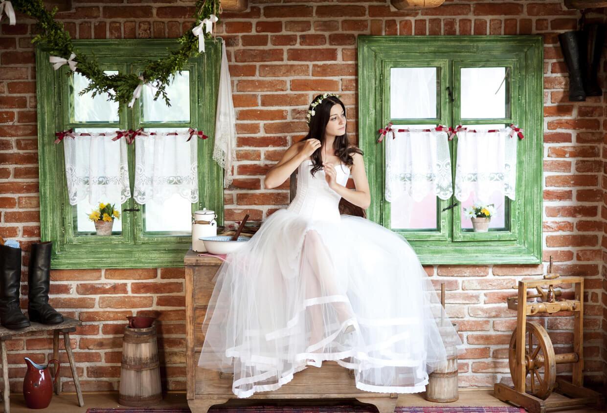 bride sitting outside in sleeveless rustic wedding dress.jpg