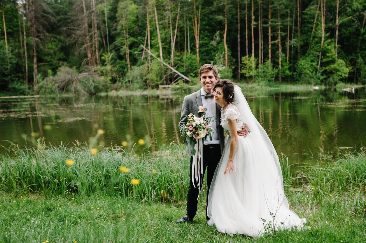 bride and groom smiling at outdoor rustic wedding venue.jpg