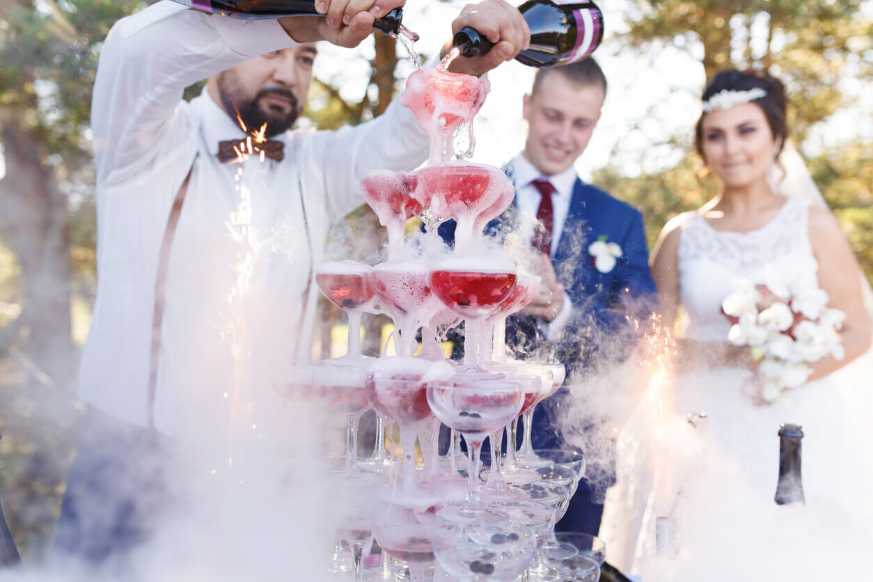 bartender pouring champagne into tower of glasses at wedding.jpg