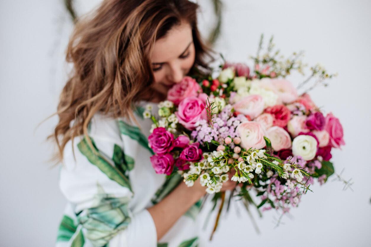 woman smelling beautiful bouquet of wedding flowers.jpg