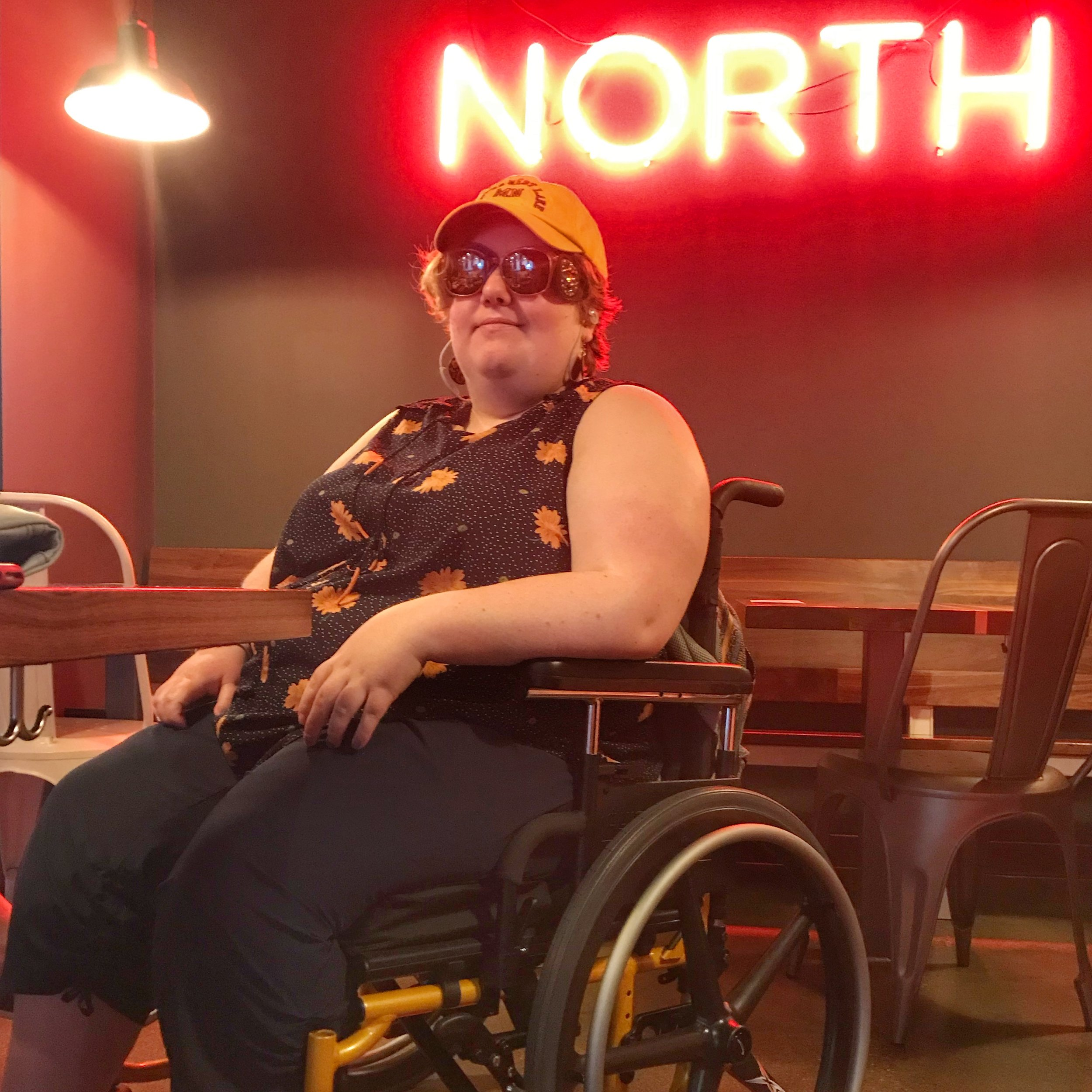 """Erin and her wheelchair """"Golden Hotwheels"""" at a brewery. The neon sign in the background reads: NORTH."""