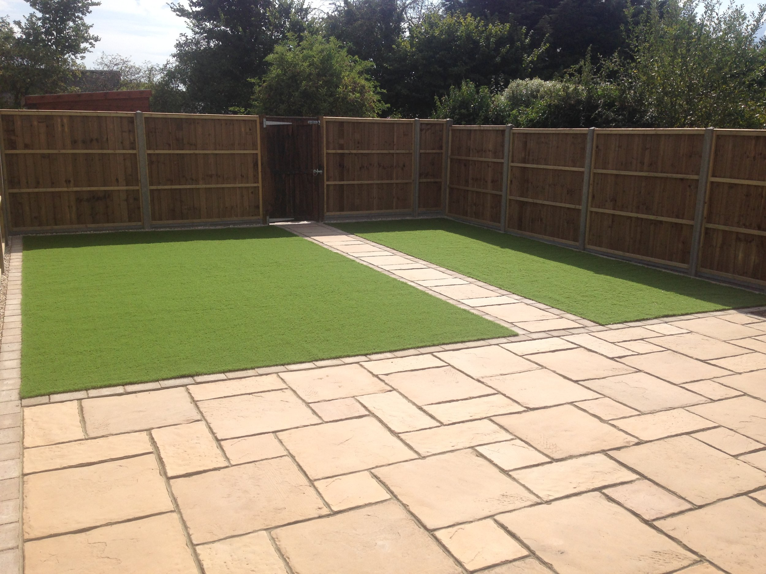 Brett Canterbury slabs were used on this patio with closed board fence panels and artificial grass