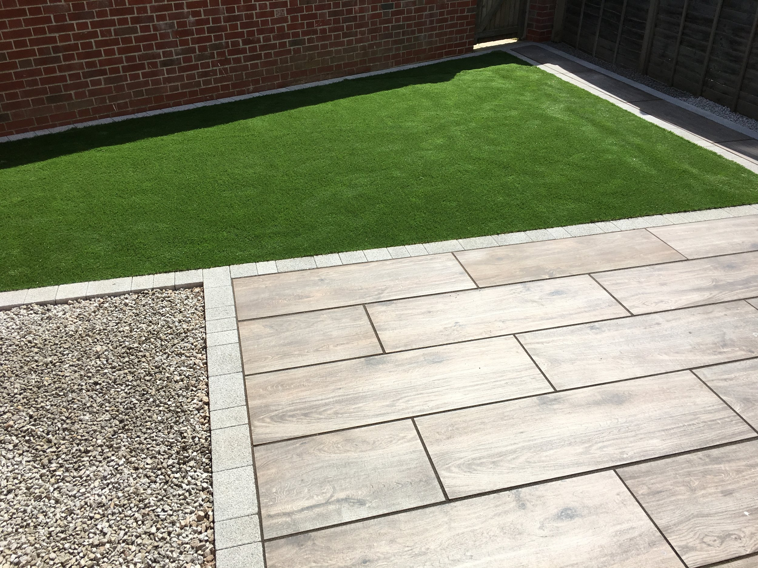 Brett Vintage oak porcelain with a Brett Lugano block was used on this patio with artificial grass
