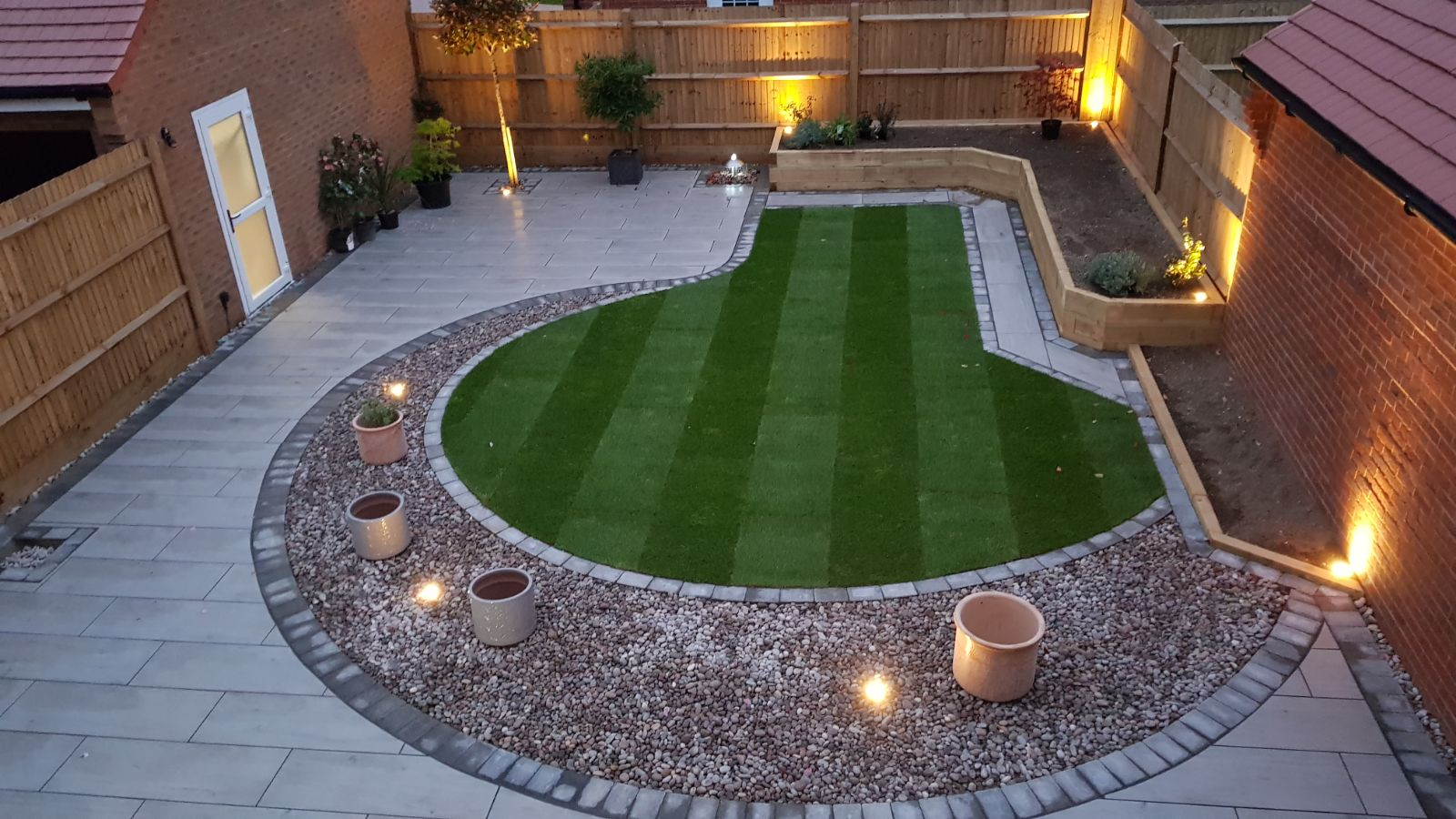 A beautiful garden transformation, where we have used porcelain paving, new turf, installed planters with sleepers and also pit lighting all around the garden, this garden was in Felpham Bognor Regis West Sussex. This patio and garden design won us second place on the Brett paving national awards ceremony.