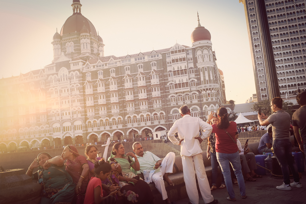 In the background is the famous  Taj Hotel.  According to legend the British architect had send the building plans to India, only to find out years later that the hotel had been built the wrong way - apparently the facade facing the sea (s. above) with its rather small entrance was meant to be the garden side, and vice versa.
