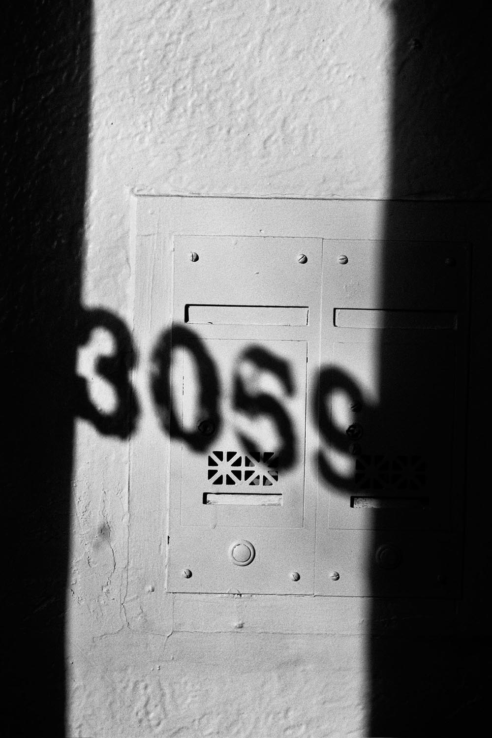 Black and white shadow of an address painted on a window.