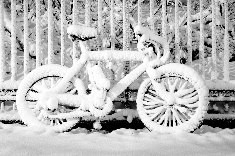 Black and white photograph of a bicycle covered in undisturbed snow.