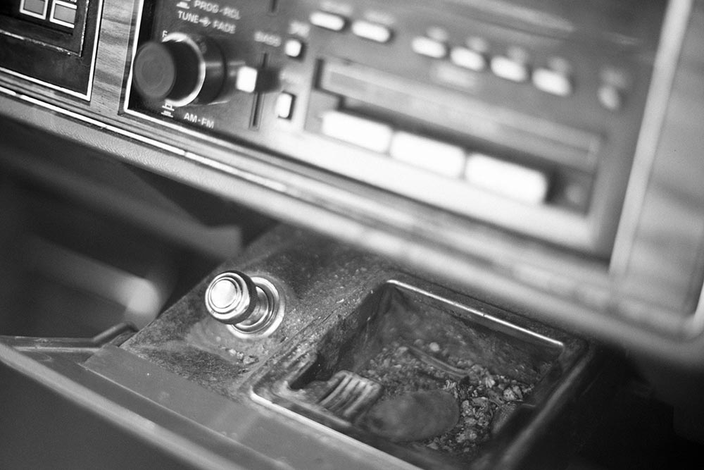Black and white photo of a cigar butt in the ashtray of a 1989 Buick Park Avenue.