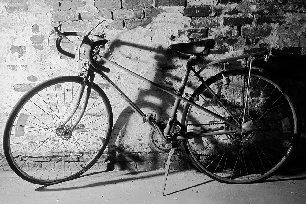 Black and white photograph of a 10-speed racing bicycle in a dusty basement.