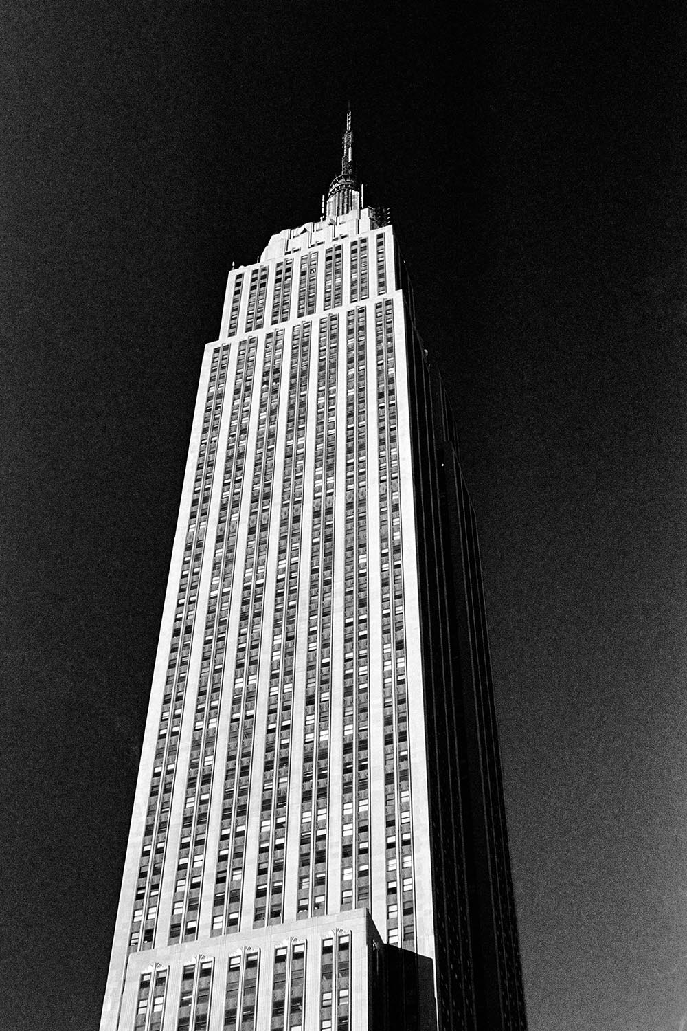 Black and white photograph of the Empire State Building set against a blackened, polarized sky.