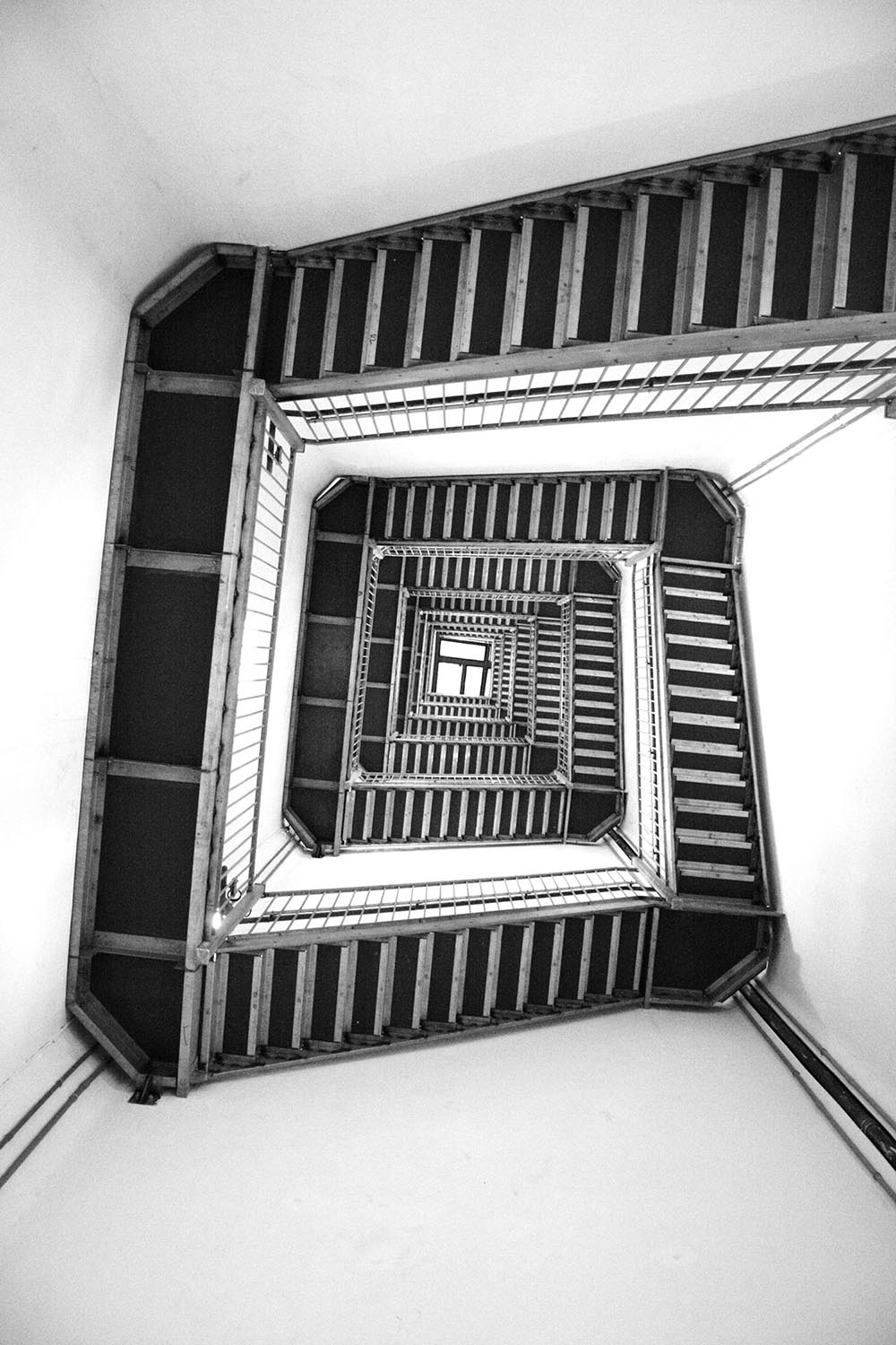 Black and white photo of a spiraling staircase in a walk-up building.