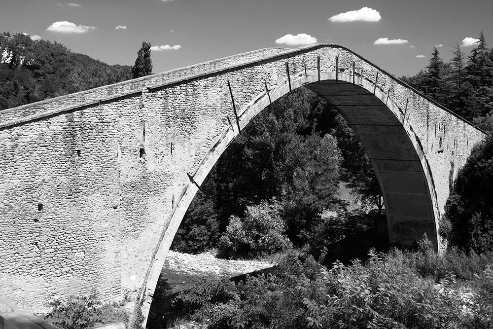Black and white photograph of the Ponte Alidosi bridge in Castel Del Rio, Italy.
