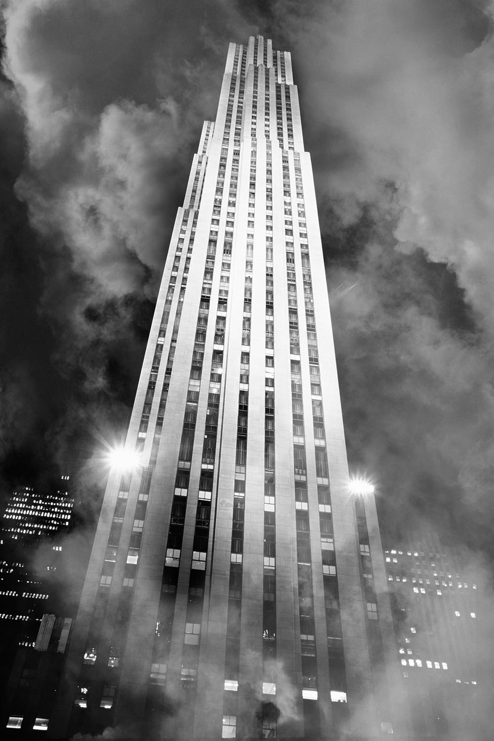 Black and white photograph of Rockefeller Center in fog at night.