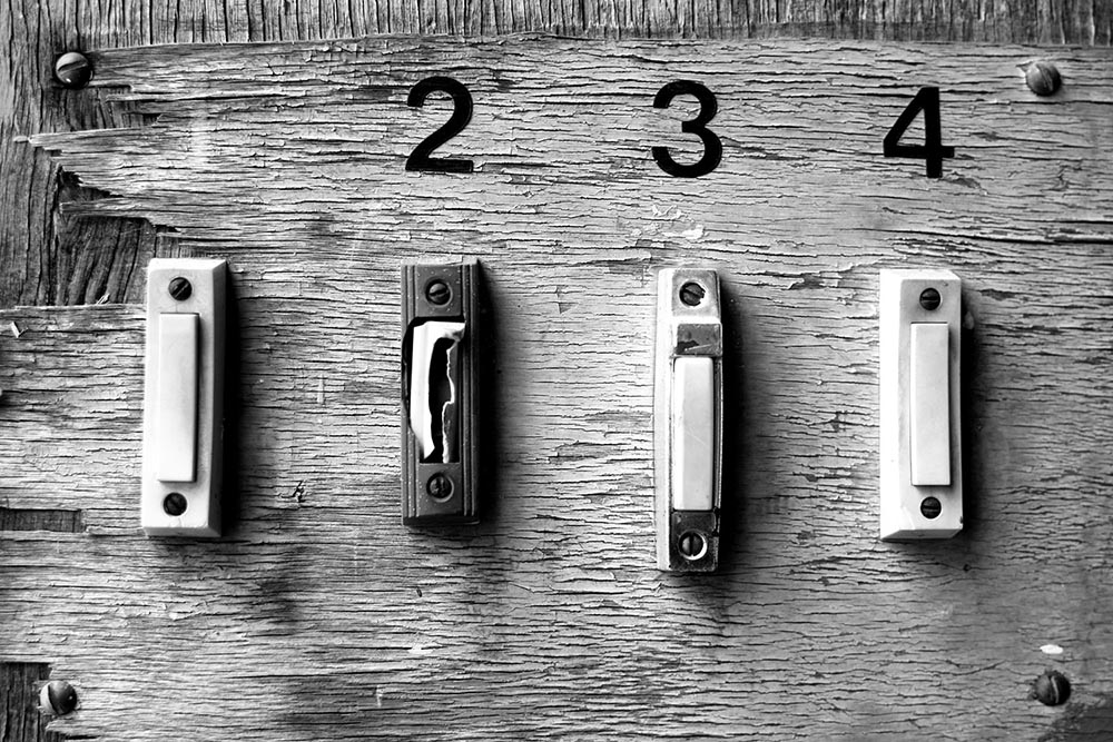 Black and white photo of four poorly-installed doorbell chimes on a piece of plywood.