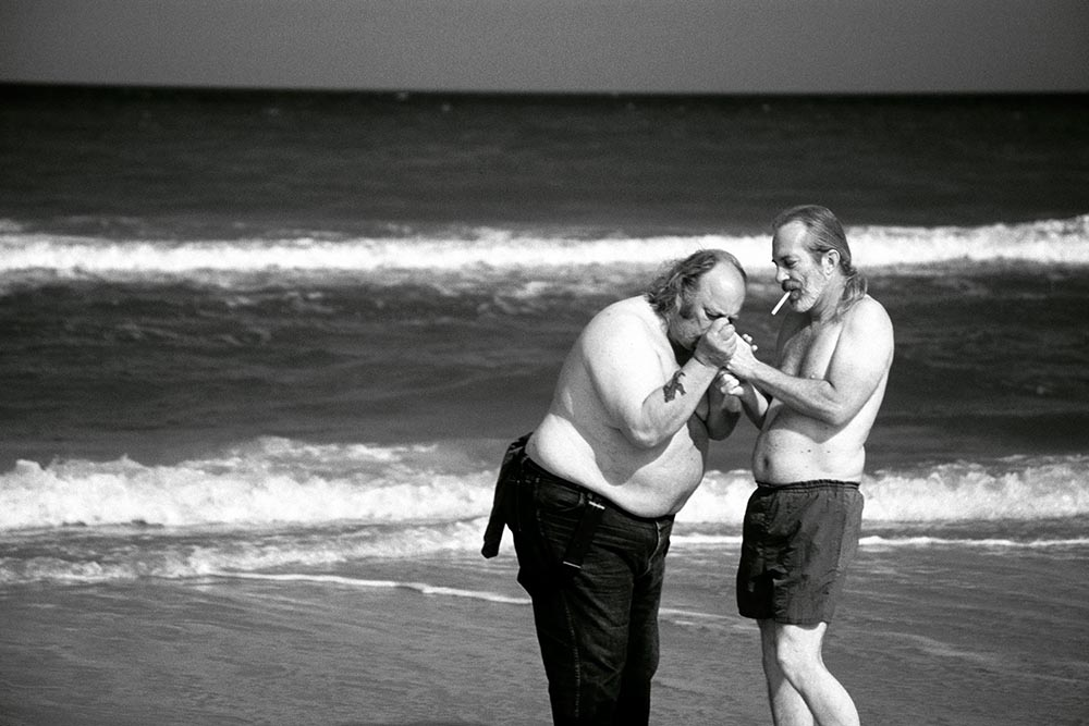 Black and white photograph of two old men smoking cigarettes at the beach.