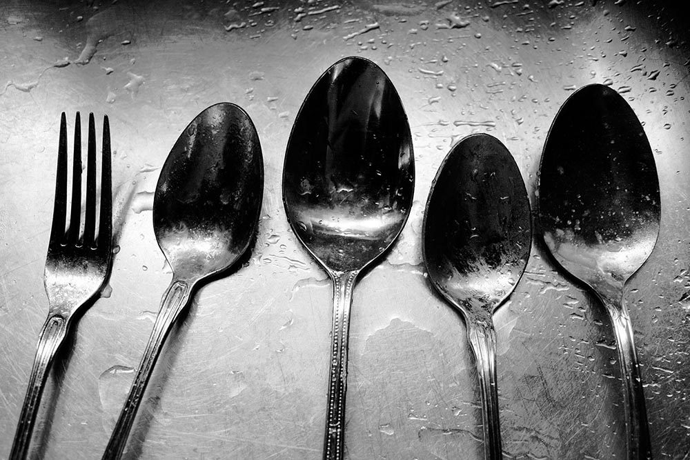 Black and white photograph of four mismatched spoons and a solitary fork.