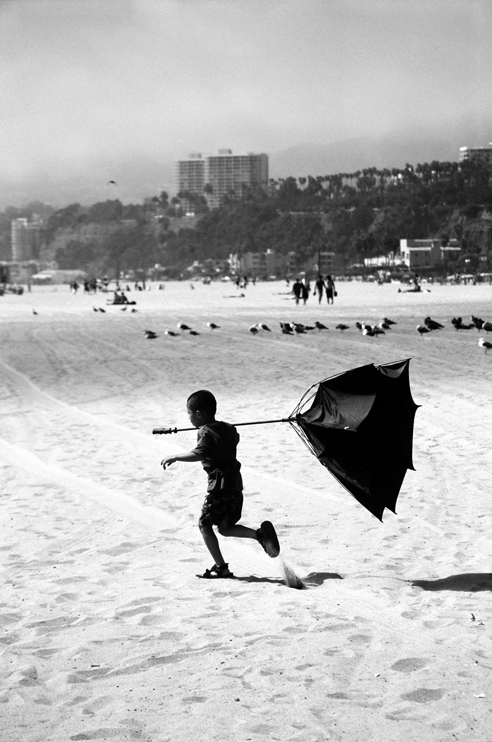 Black and white photograph of a young boy running on the beach with an inside out umbrella.