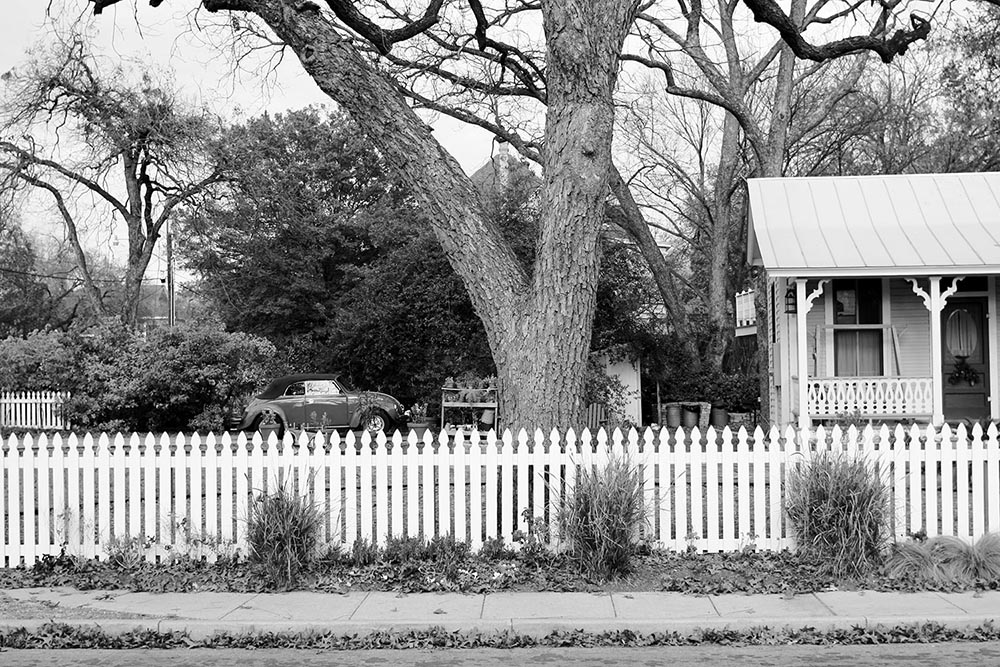 Black and white photo of a white picket fence.