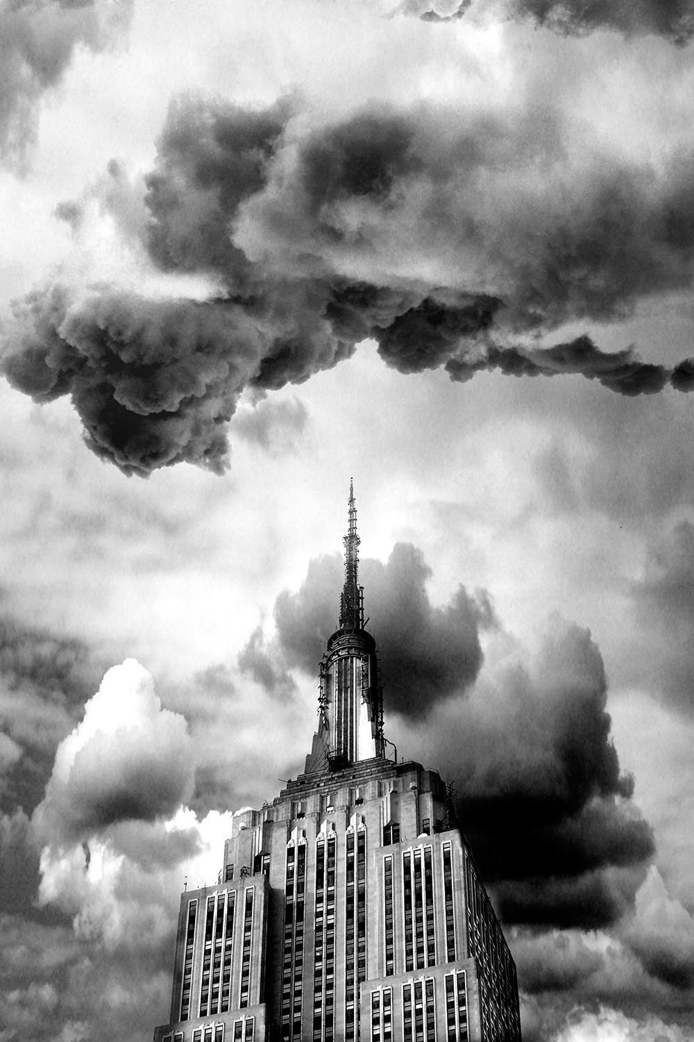 Black and white photograph of dramatic storm clouds gathering above and behind the Empire State Building.