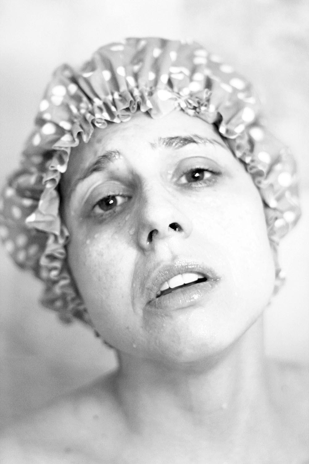 Black and white photo of a woman in a shower cap.
