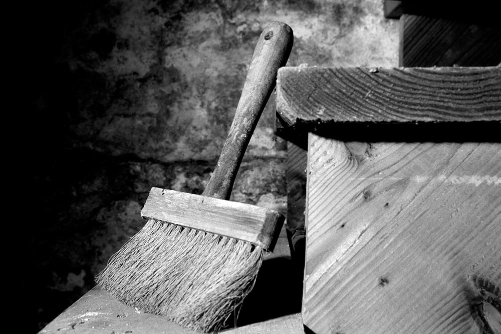 Black and white photograph of an antique wooden paintbrush.
