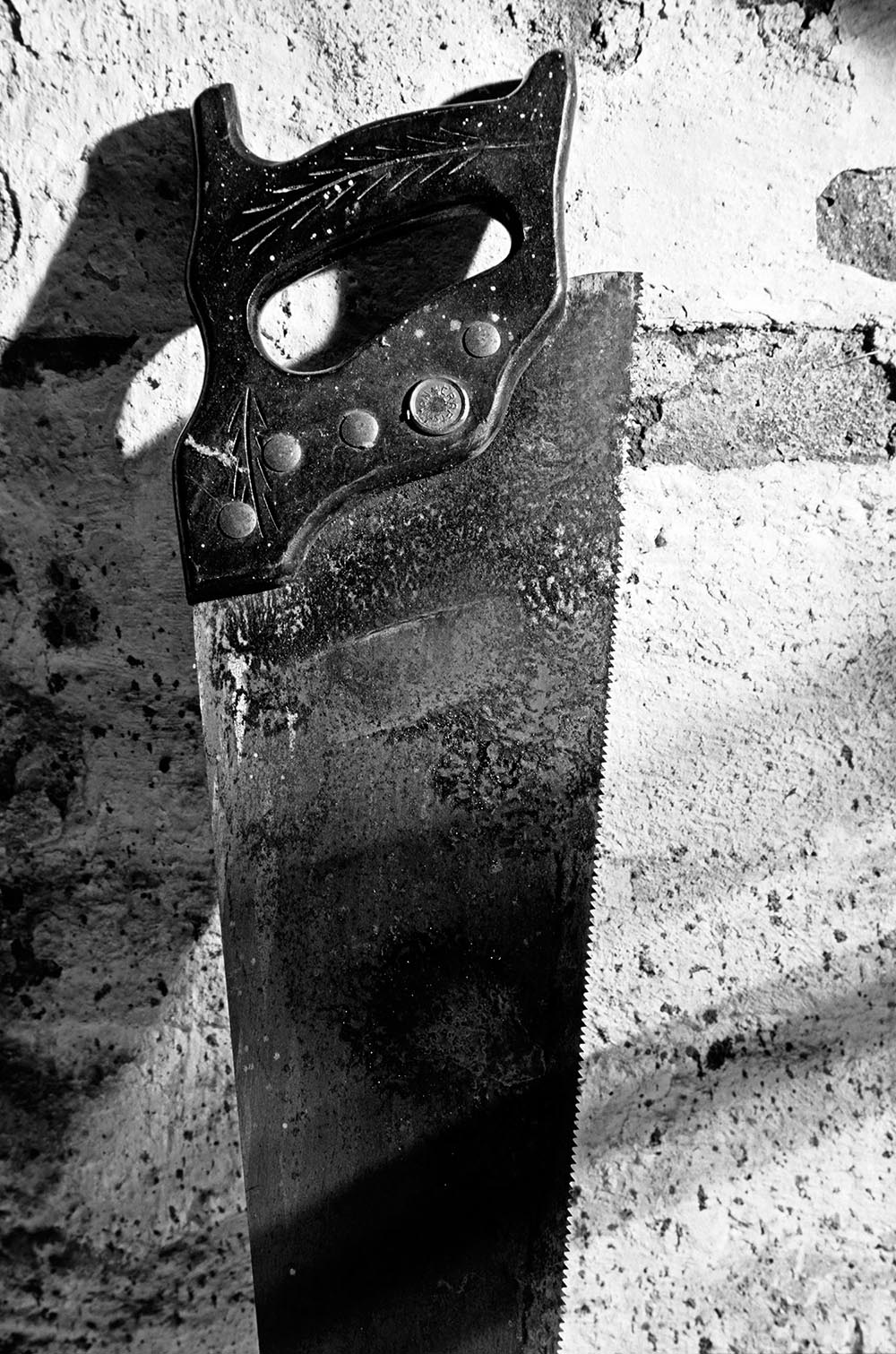 Black and white photograph of an old rusted saw with worn down teeth.